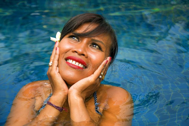 Outdoors lifestyle portrait of middle aged 40s or 50s attractive and happy Asian Indonesian woman in biking enjoying holidays at. Bali villa or tropical resort royalty free stock photography