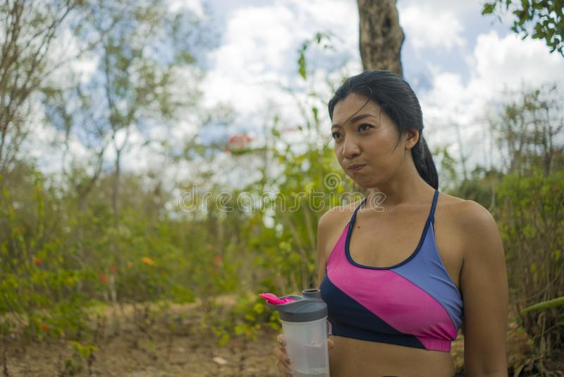Outdoors lifestyle portrait of young attractive tired and thirsty Asian woman drinking water after hard running workout cooling royalty free stock photography