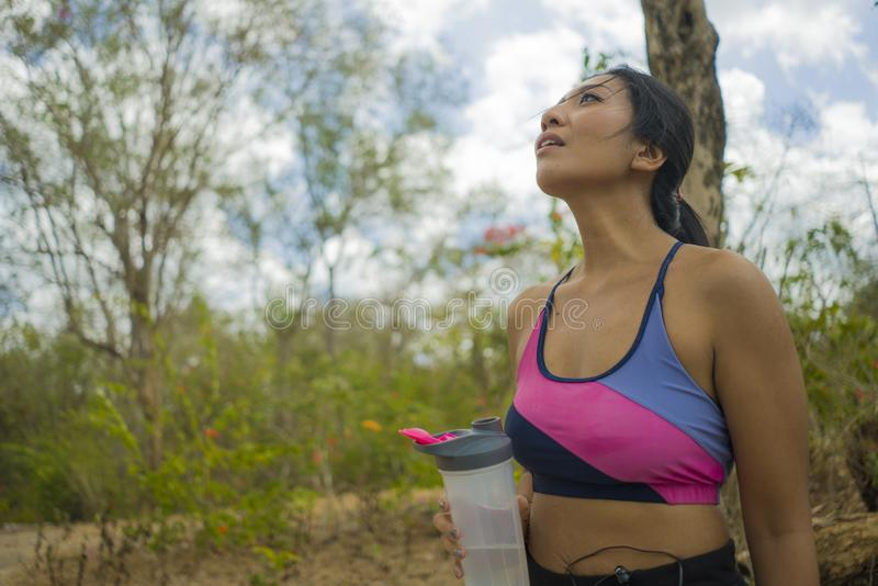 Outdoors lifestyle portrait of young attractive tired and thirsty Asian woman drinking water after hard running workout cooling royalty free stock photos