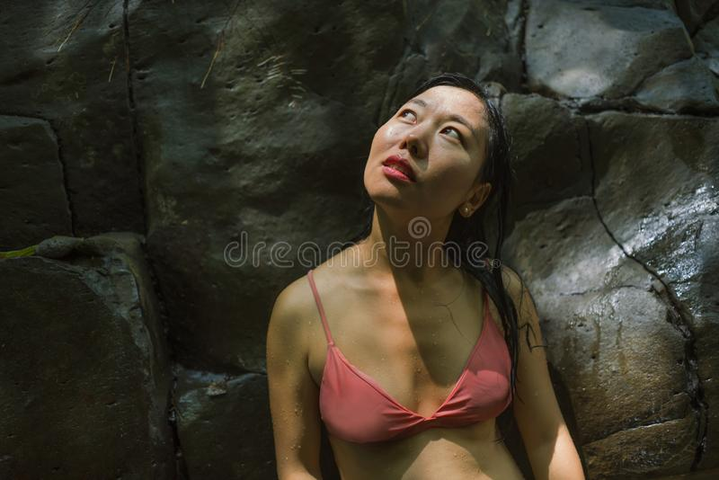 Outdoors lifestyle portrait of young beautiful and happy Asian Chinese woman in bikini enjoying Summer holidays at tropical forest royalty free stock photos