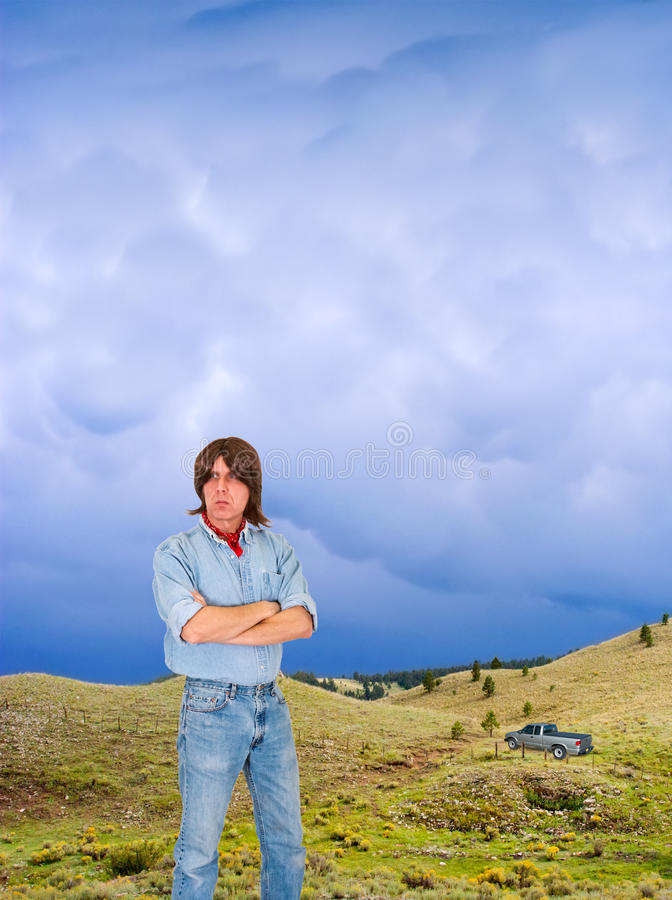Outdoors Man With Pickup Truck in Wild Nature. A man with long brown hair stands in a western landscape and enjoys the outdoors. In the distance is a passing stock images