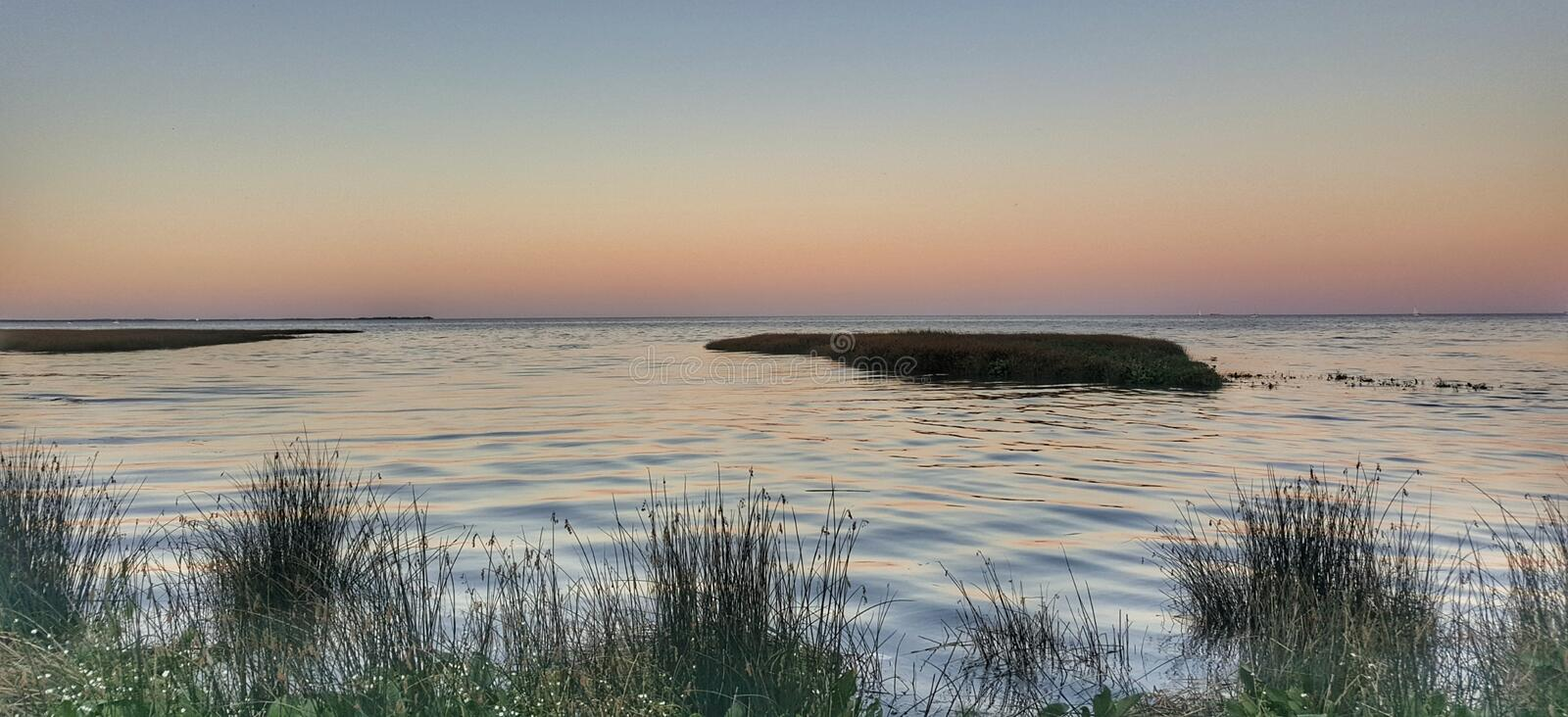 Outdoors nature landscape no people calm river water green vegetation at sunset blue and pink sky still life. Outdoors nature landscape no people calm river royalty free stock photography