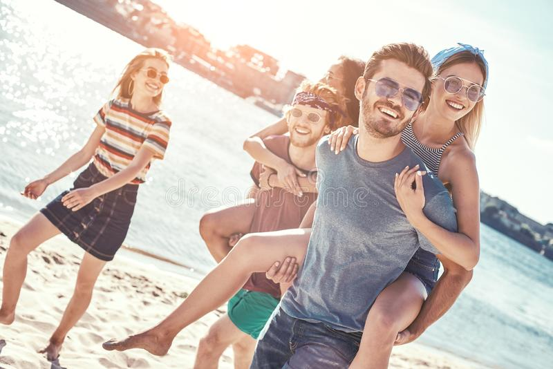 Outdoors photo of happy boyfriends piggybacking their girlfriends at sunset on beach stock photo