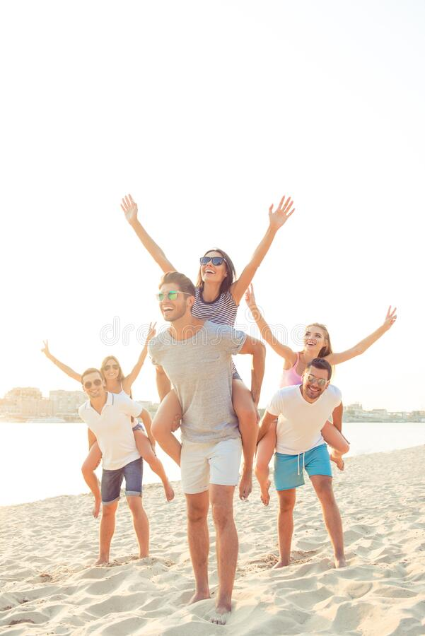 Outdoors photo of joyful smiling boyfriends piggybacking their girlfriends while rise hands at sunset on beach.  royalty free stock image