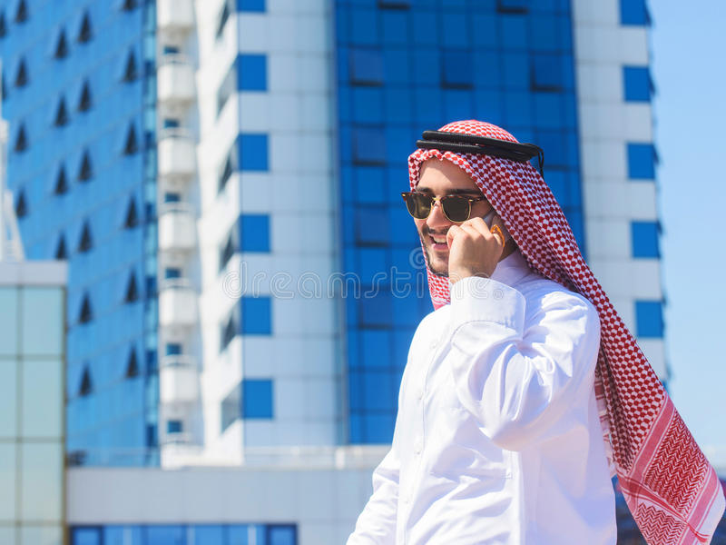 Outdoors portrait of an arabian man talking on a cell ph stock photography