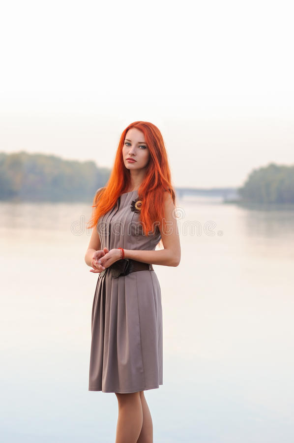 Outdoors portrait of beautiful confident woman with red hair, co royalty free stock photography