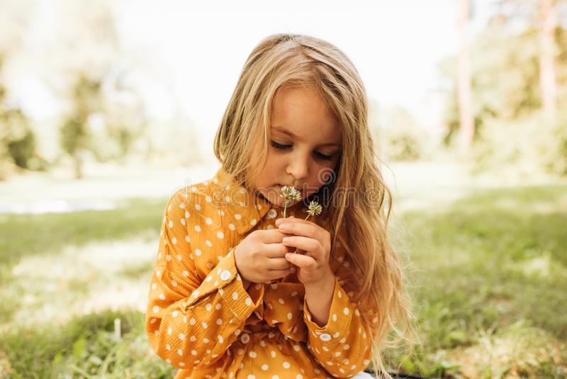 Outdoors portrait of beautiful little girl with long blonde hair smelling flowers for her mother at nature background. Happy child stock photo