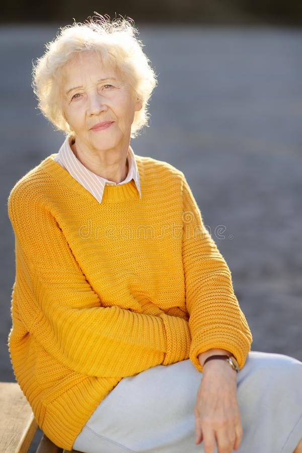 Outdoors portrait of beautiful smiling senior woman with curly white hair. Elderly lady walking in autumn park royalty free stock image