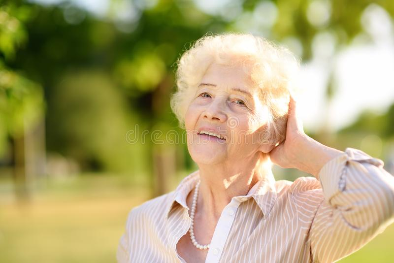 Outdoors portrait of beautiful smiling senior woman with curly white hair royalty free stock photography