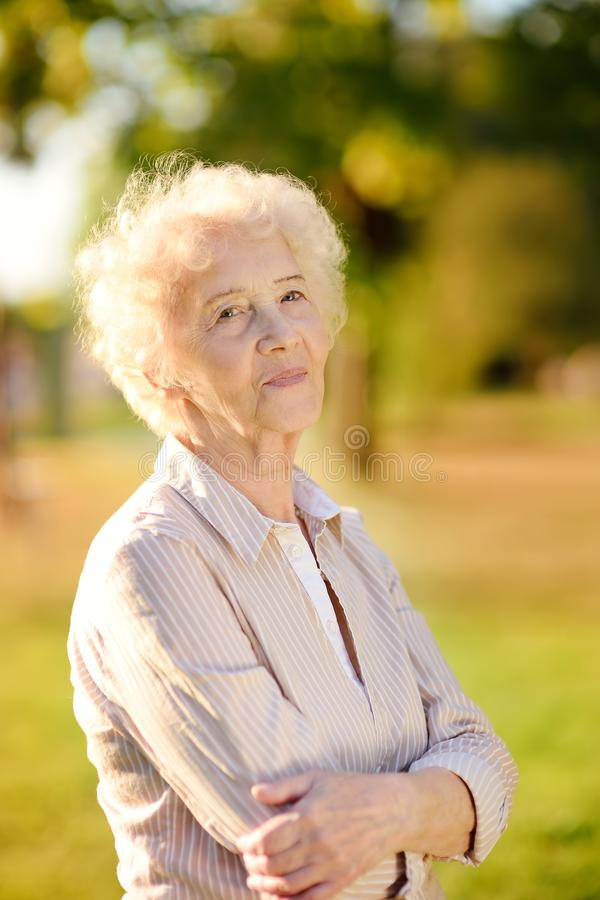 Outdoors portrait of beautiful smiling senior woman with curly white hair royalty free stock photos