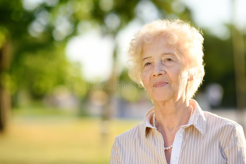 Outdoors portrait of beautiful smiling senior woman with curly white hair royalty free stock photo