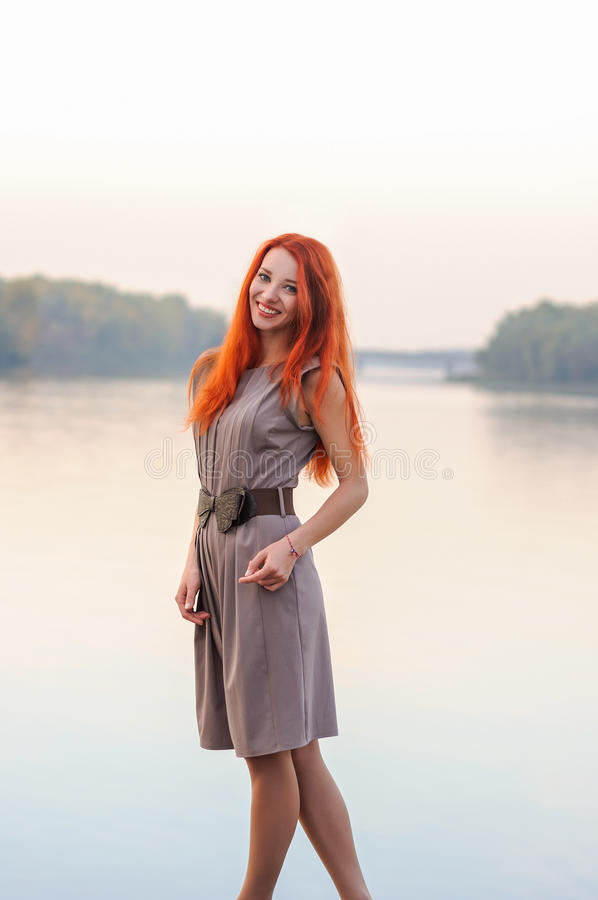 Outdoors portrait of beautiful smiling woman with red hair, colo royalty free stock photo