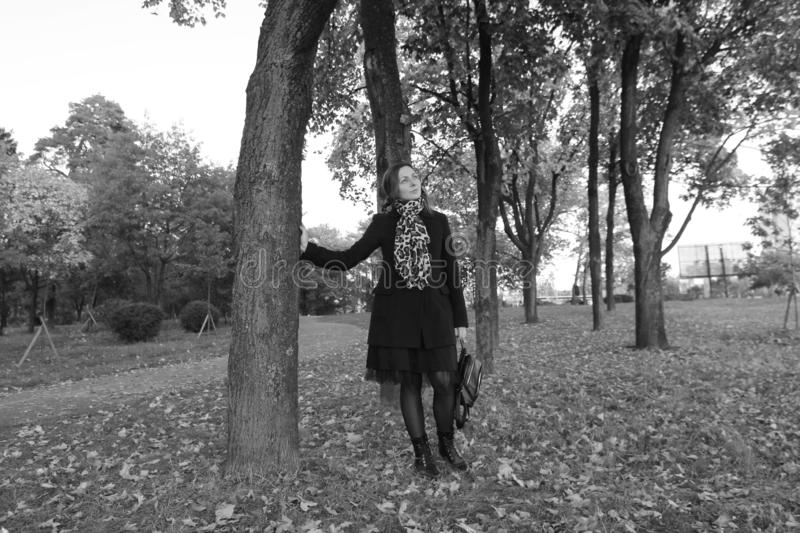 Outdoors portrait of beautiful young woman posing in autumn garden. Black-white photo. royalty free stock photography