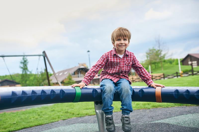 Outdoors portrait of cute preschool smiling boy swinging on a swing at the playground royalty free stock images