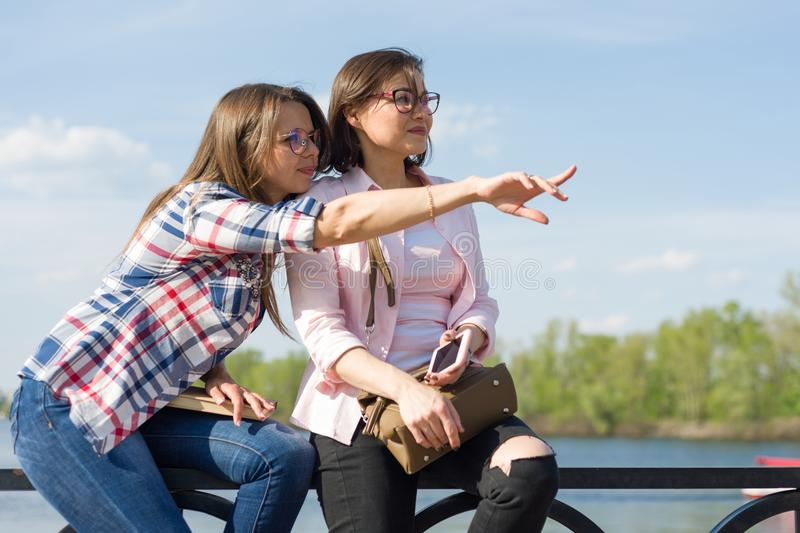 Outdoors portrait of female friends. Background nature, park, river. Urban lifestyle and friendship concept. stock photos