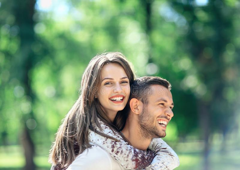 Outdoors portrait of lovers happy young man and woman. Outdoors portrait of lovers happy young men and women looking at camera. Smiling girl piggyback of her royalty free stock photo