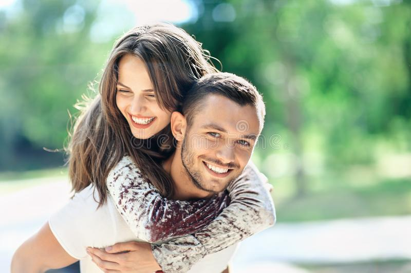 Outdoors portrait of lovers happy young man and woman. Outdoors portrait of lovers happy young men and women looking at camera. Smiling girl piggyback of her stock photography