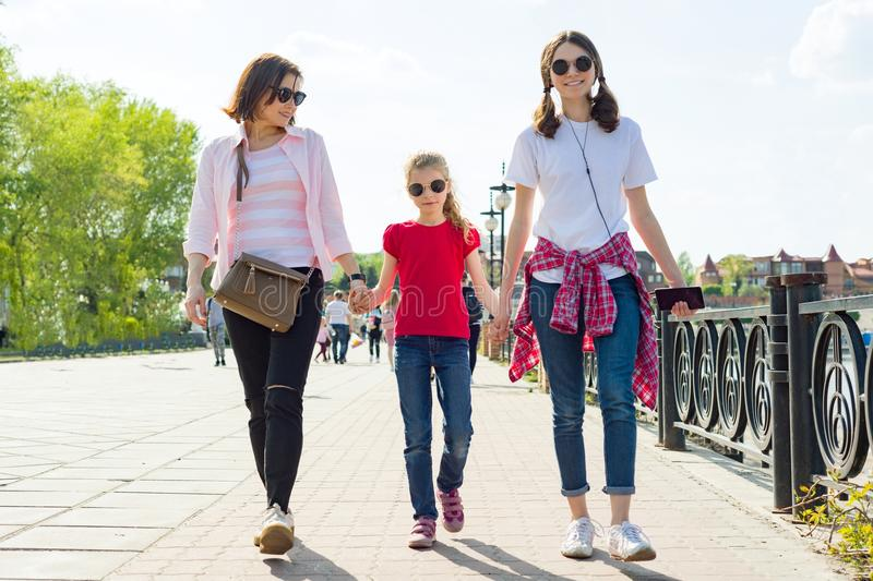 Outdoors portrait of mother and two daughters. stock photo