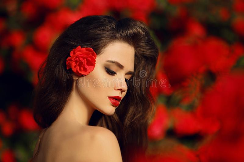 Outdoors portrait of Natural Beauty woman in red roses. Sensual royalty free stock images