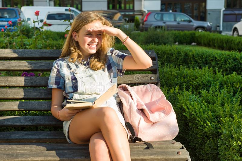Outdoors portrait of teenage schoolgirl 13, 14 years old sitting on bench in city park with book. stock photos