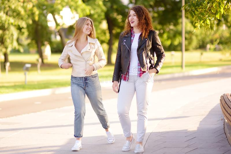 Outdoors portrait of two delightful young woman. Two caucasian girls friend stroll and chat together in sunny day. Friendship stock image