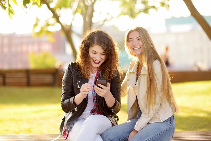 Outdoors portrait of two delightful young woman. Variety of female beauty. Two caucasian girls friend stroll together in sunny day stock photography