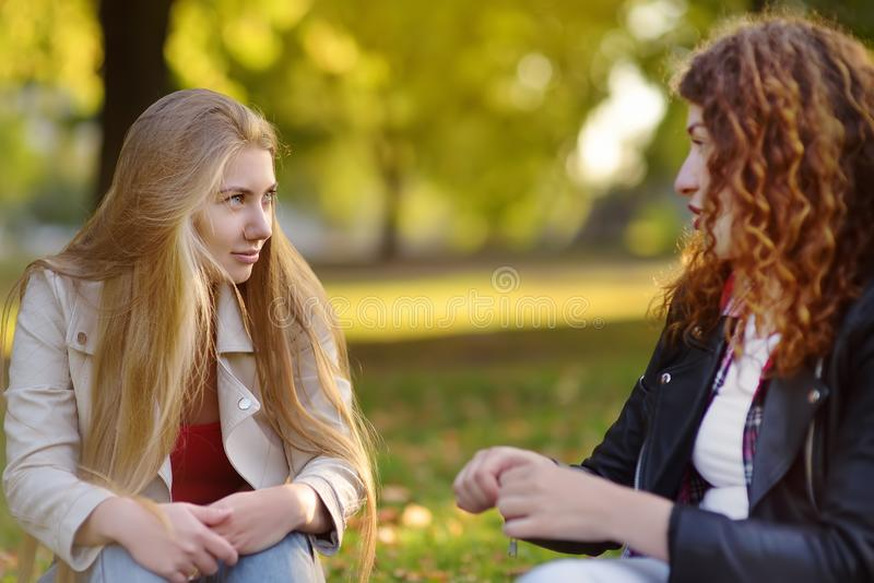 Outdoors portrait of two delightful young woman. Variety of female beauty. Two caucasian girls friend stroll together in sunny day. Girlfriends. Communication stock photography