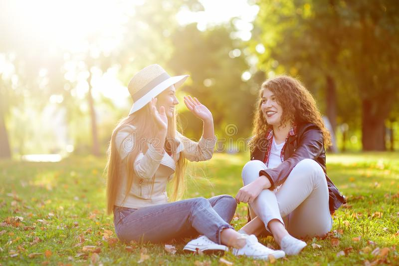 Outdoors portrait of two delightful young woman. Variety of female beauty. Two caucasian girls friend stroll together in sunny day. Girlfriends. Communication stock photo