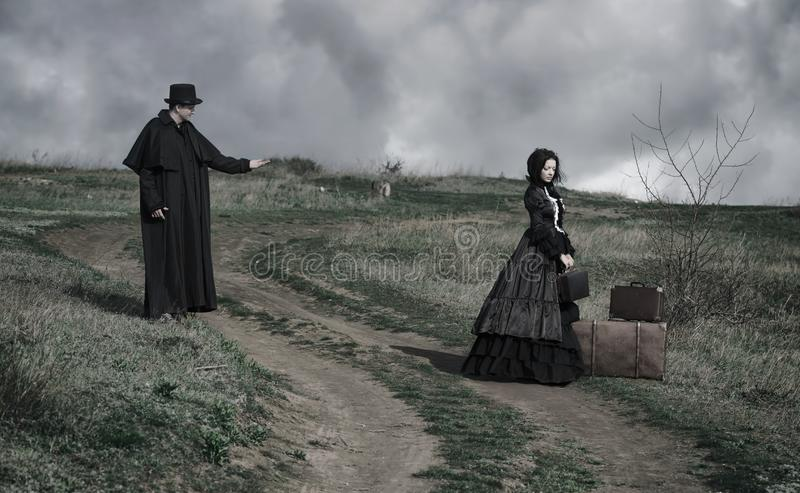 Portrait of a victorian lady in black sitting on the road with her luggage and gentleman standing nearby. royalty free stock images