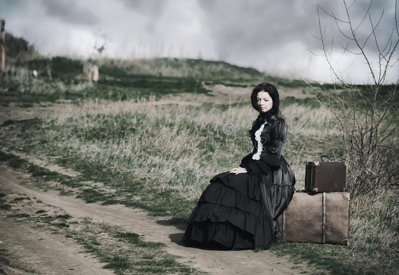 Outdoors portrait of a victorian lady in black sitting alone on the road with her luggage royalty free stock photos