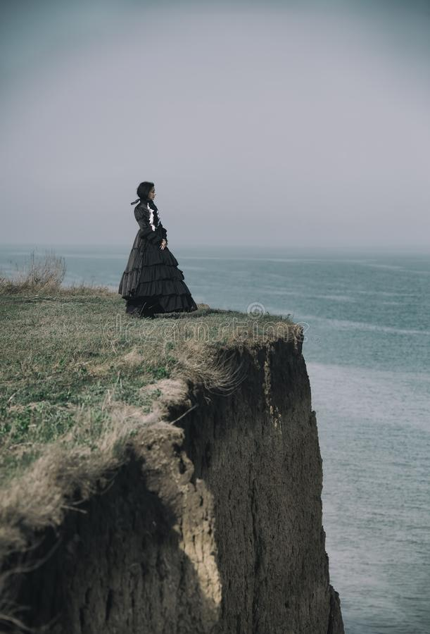 Outdoors portrait of a victorian lady in black standing on the cliff stock image
