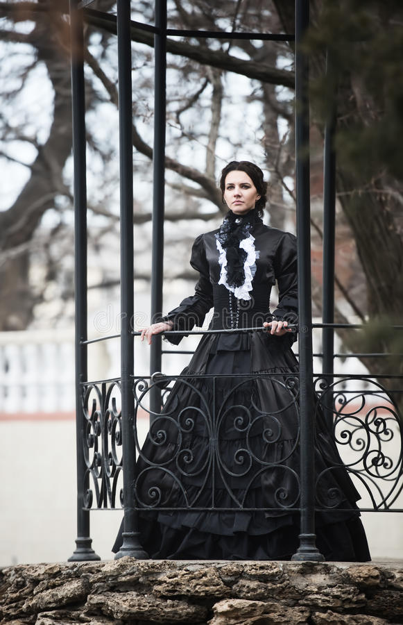 Outdoors portrait of a victorian lady in black stock photography