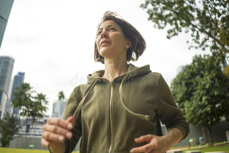 Outdoors portrait of young attractive and active jogger woman in hoodie top running and jogging in morning workout at beautiful stock image