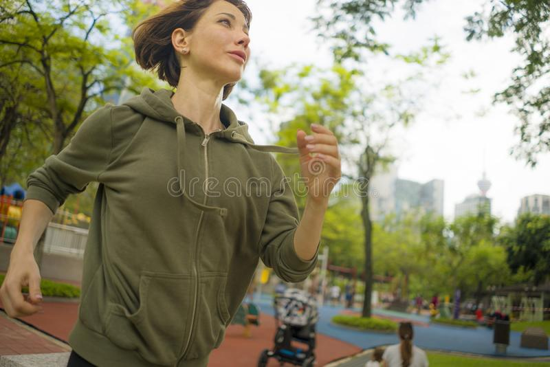 Outdoors portrait of young attractive and active  jogger woman in hoodie top  running and jogging in morning workout at beautiful royalty free stock photo