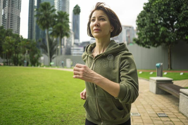 Outdoors portrait of young attractive and active  jogger woman in hoodie top  running and jogging in morning workout at beautiful stock photography