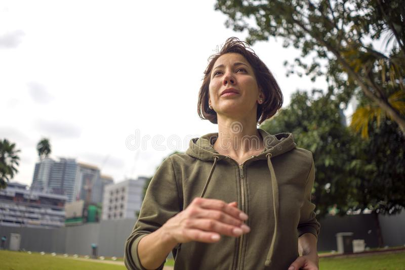 Outdoors portrait of young attractive and active  jogger woman in hoodie top  running and jogging in morning workout at beautiful royalty free stock photography