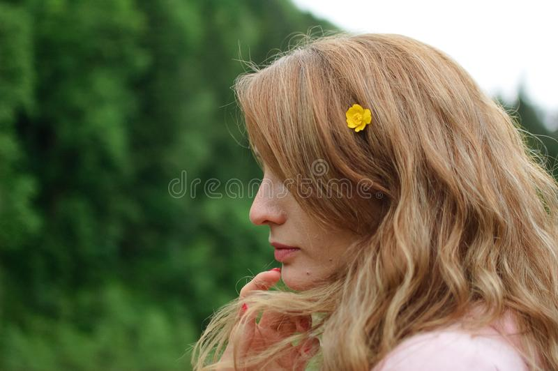 Outdoors portrait of young calm blonde woman in pink clothes with little yellow flower in her long hair on the hill with. Portrait of young calm blonde woman in stock photos