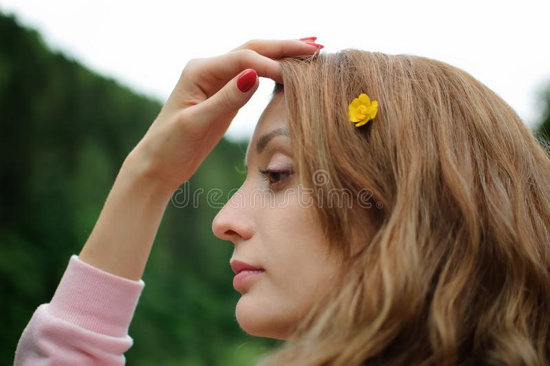 Outdoors portrait of young calm blonde woman in pink clothes with little yellow flower in her long hair on the hill with. Portrait of young calm blonde woman in stock photo