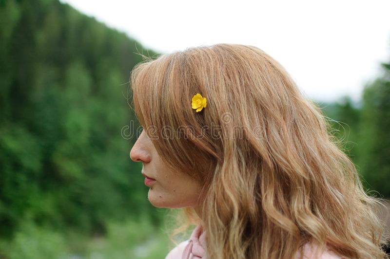 Outdoors portrait of young calm blonde woman in pink clothes with little yellow flower in her long hair on the hill with. Portrait of young calm blonde woman in royalty free stock photography