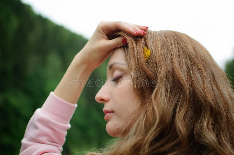 Outdoors portrait of young calm blonde woman in pink clothes with little yellow flower in her long hair on the hill with. Portrait of young calm blonde woman in stock image