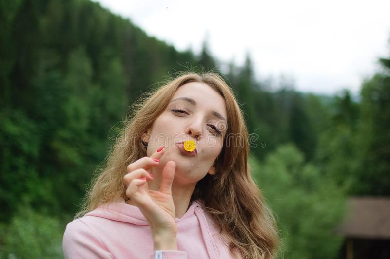 Outdoors portrait of young calm blonde woman in pink clothes with little yellow flower in her mouth on the hill with. Portrait of young calm blonde woman in pink royalty free stock image