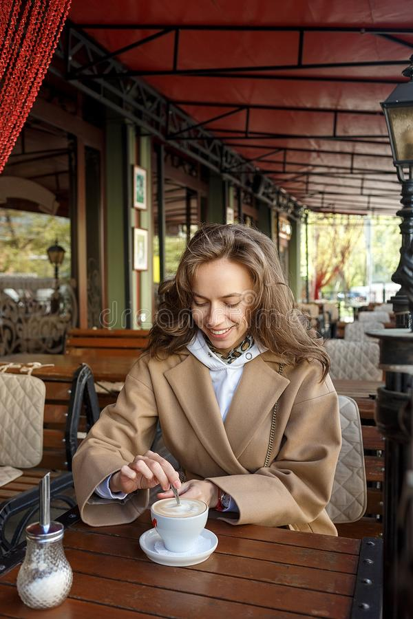Outdoors portrait of young smiling girl wearing beige coat drinking coffee on cafe veranda stiring sugar with a spoon stock photo