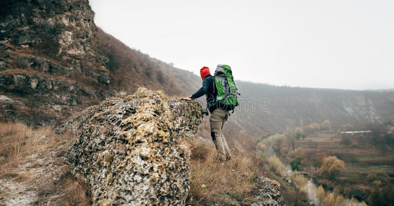 Outdoors rear view of hiker man hiking in mountains in cloudy day. Traveler male with big backpack and red hat stock photos