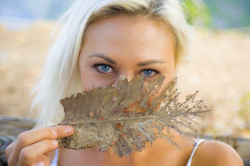 Outdoors romantyczny portret młoda piękna i szczęśliwa blond dziewczyna z wspaniałymi niebieskimi oczami bawić się z jesień liści zdjęcie royalty free