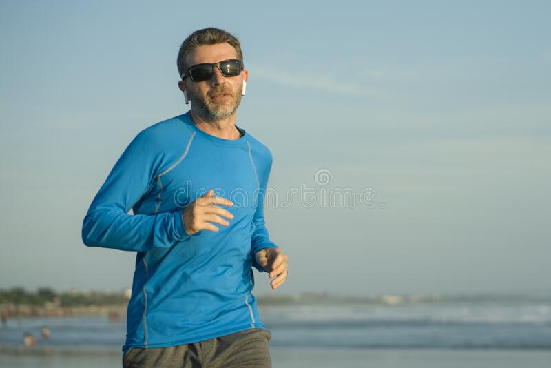 Outdoors running workout - young attractive and athletic runner man jogging on beautiful beach in Summer training happy and free royalty free stock photo