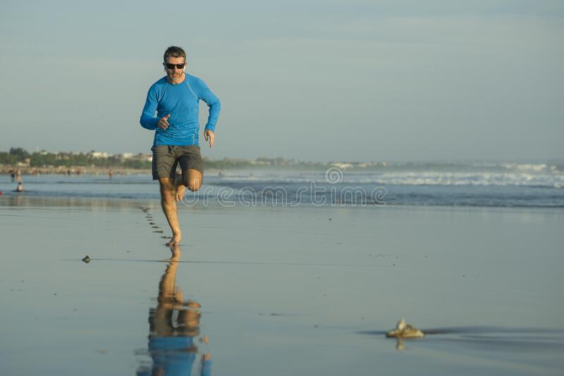 Outdoors running workout - young attractive and athletic runner man jogging on beautiful beach in Summer training happy and free stock images