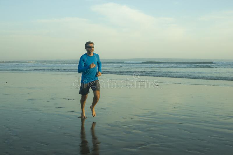 Outdoors running workout - young attractive and athletic runner man jogging on beautiful beach in Summer training happy and free stock photos