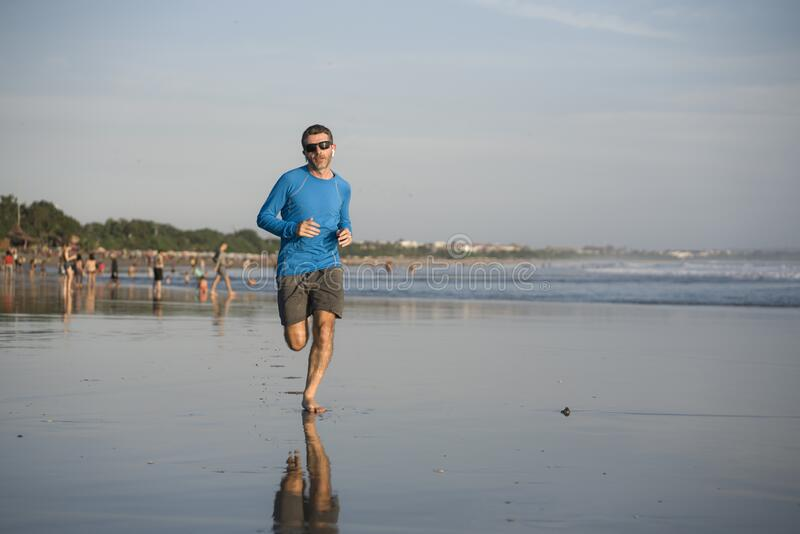 Outdoors running workout - young attractive and athletic runner man jogging on beautiful beach in Summer training happy and free royalty free stock image