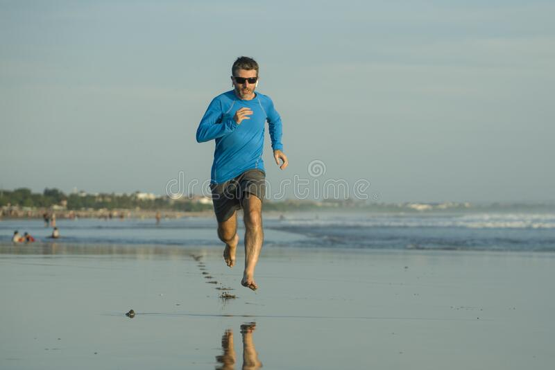 Outdoors running workout - young attractive and athletic runner man jogging on beautiful beach in Summer training happy and free stock photography