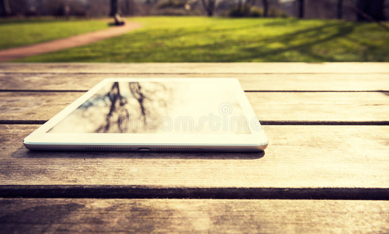 Outdoors rustic wooden table with digital tablet, reflecting trees, with copy space. Rustic wooden table with digital tablet and trees reflecting on black screen stock image